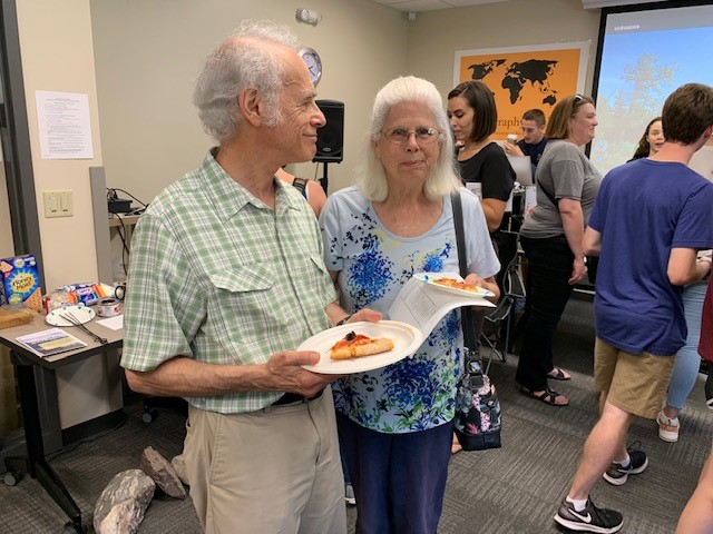 Couple enjoy pizza at # Explore Geography Open House, which was attended by more than 100 individuals.